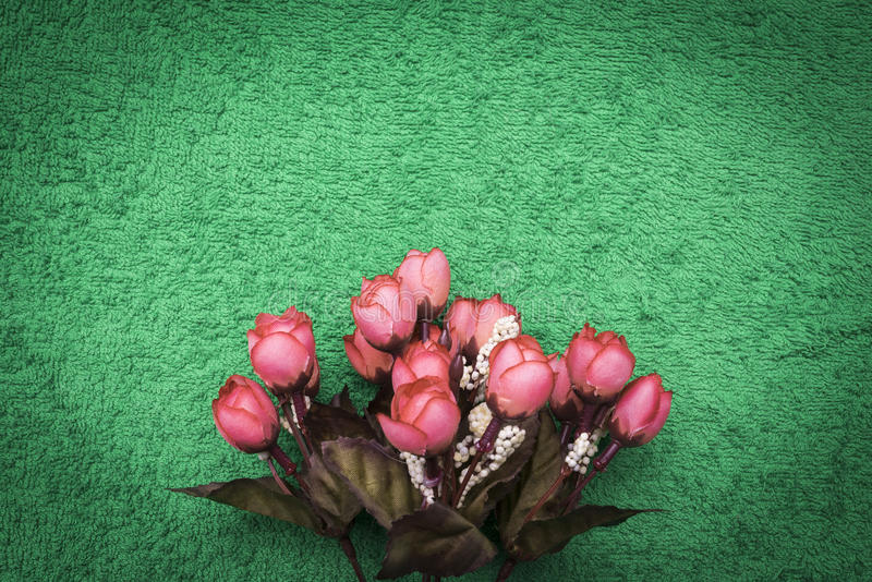 Flores artificiales rosadas en un fondo de la verde-esmeralda ilustración del vector