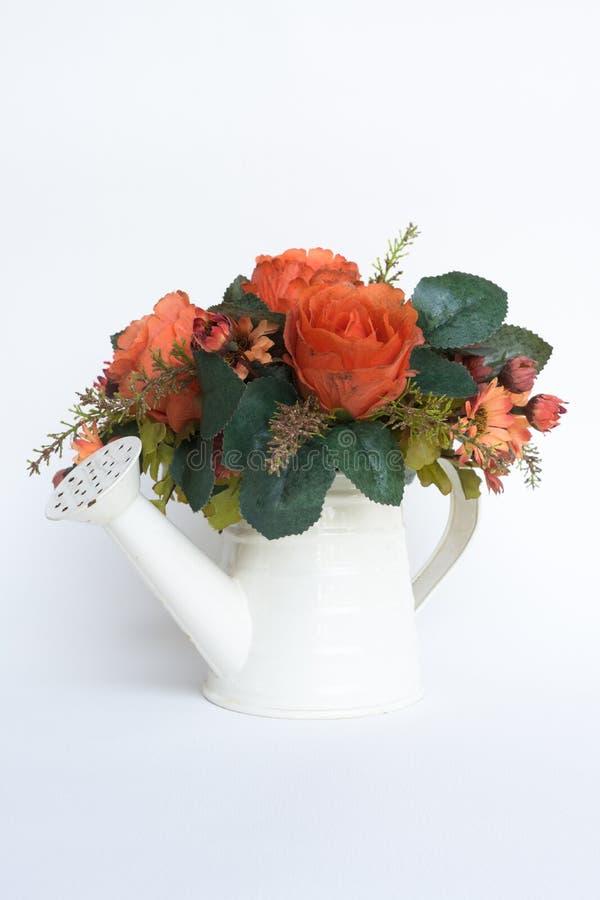 Flores artificiales viejas en waterpot blanco aherrumbrado en blanco fotos de archivo libres de regalías