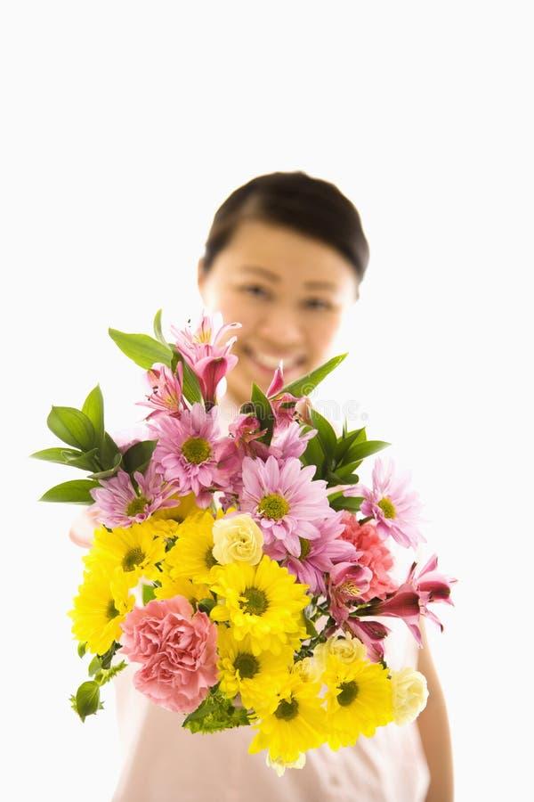 Flores asiáticas da terra arrendada da mulher. fotografia de stock