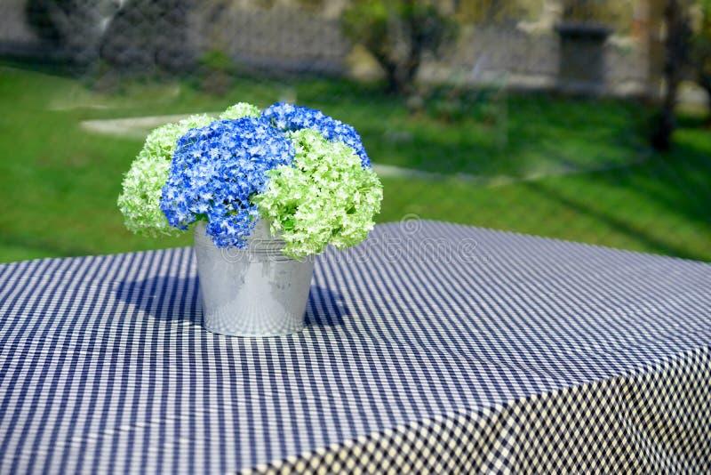 Flores azules y verdes en florero del cubo en la cubierta de tabla por la tabla mA foto de archivo