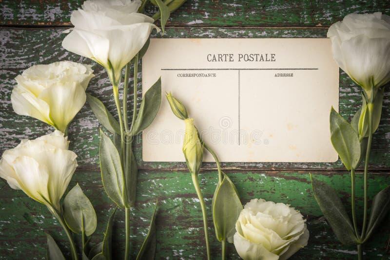 Flores blancas con la postal en la tabla de madera lamentable imágenes de archivo libres de regalías