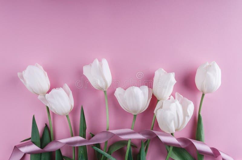 Flores blancas de los tulipanes sobre fondo rosa claro Tarjeta de felicitación o invitación de la boda imagenes de archivo