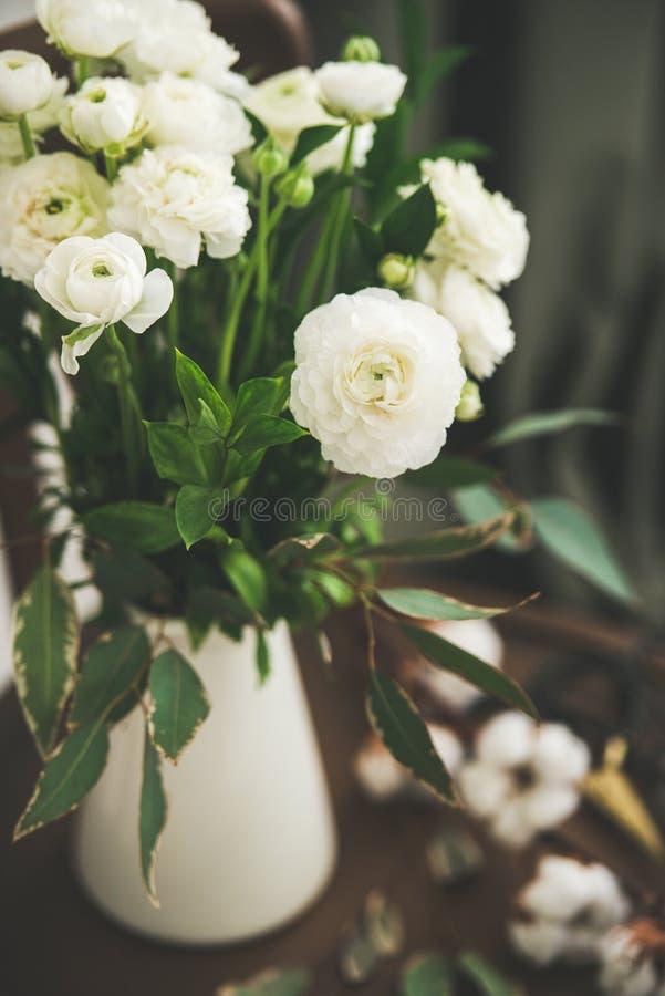 Flores blancas del ranúnculo de la primavera en jarro del esmalte con la cortina detrás imagenes de archivo
