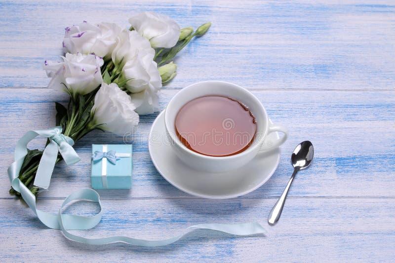 Flores blancas hermosas Ramo del Eustoma con té y regalo en una tabla de madera azul fotografía de archivo libre de regalías