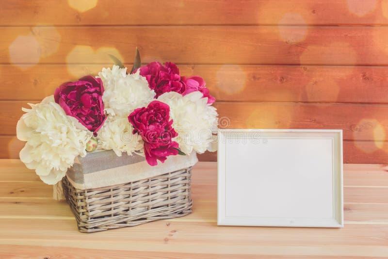 Flores blancas y rojas de la peonía en cesta de mimbre y el marco blanco en la tabla de madera foto de archivo libre de regalías
