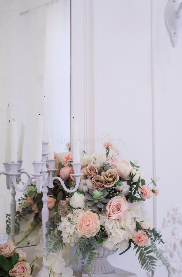 Flores bonitas e à moda em um suporte de vidro do vaso perto de um espelho imagem de stock