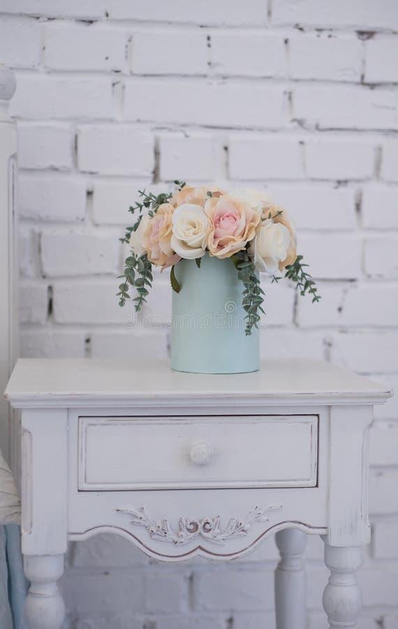 Flores bonitas em uma caixa da cor e do suporte azuis macios em um suporte de madeira cinzelado o interior nas meninas da sala foto de stock royalty free