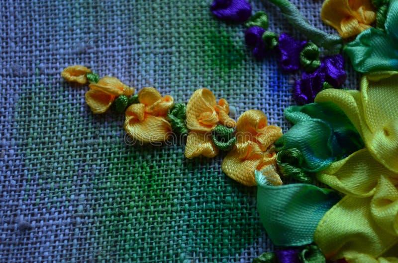 Flores bordadas com as fitas do cetim da cor na tela imagens de stock royalty free