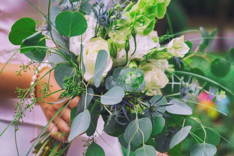 Flores brancas bonitas no bride& x27; s entrega-o delicadamente A noiva vestiu-se no branco puro em seu dia especial fotos de stock royalty free