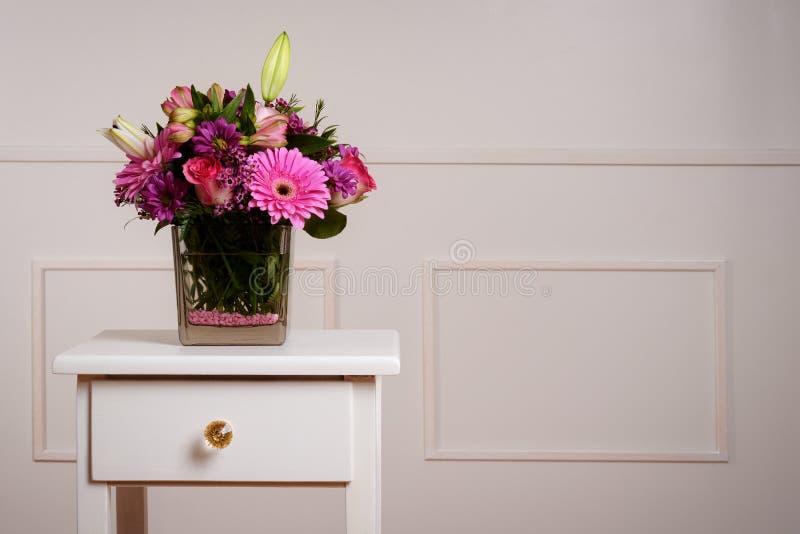 Flores clasificadas en el florero de cristal en la tabla fotografía de archivo libre de regalías