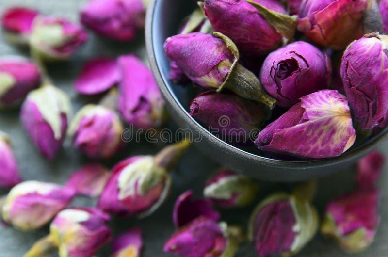 Flores color de rosa secas de los brotes en un cierre del cuenco para arriba Ingrediente asiático para la infusión de hierbas del imágenes de archivo libres de regalías