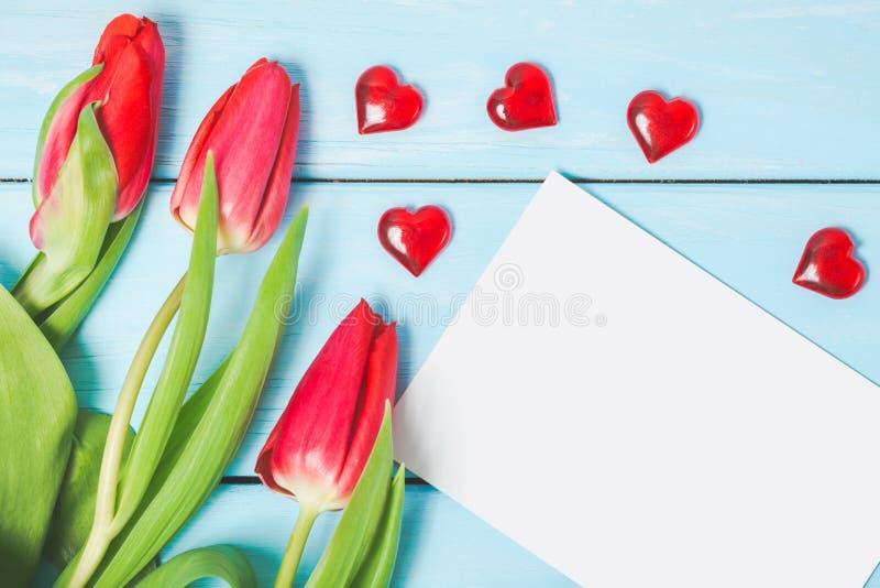 Flores coloridas del tulipán de la primavera con la foto en blanco y corazones rojos decorativos en fondo de madera azul claro co fotografía de archivo libre de regalías