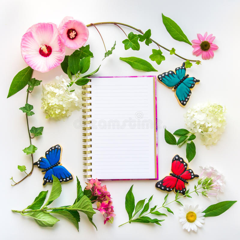 Flores coloridas e cookies caseiros da borboleta, composit floral imagens de stock