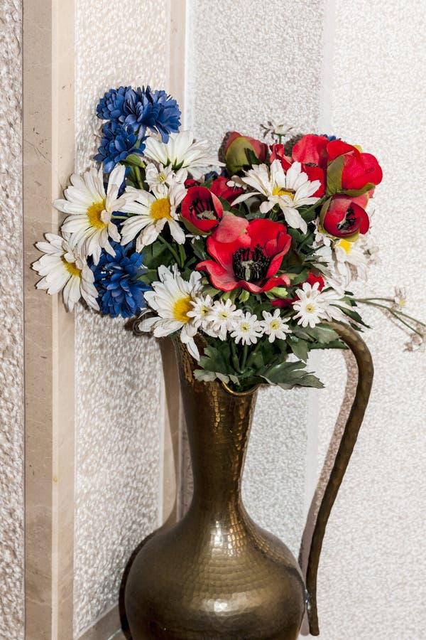 Flores coloridas em uma fotografia de bronze do caraff em casa - fotografia de stock