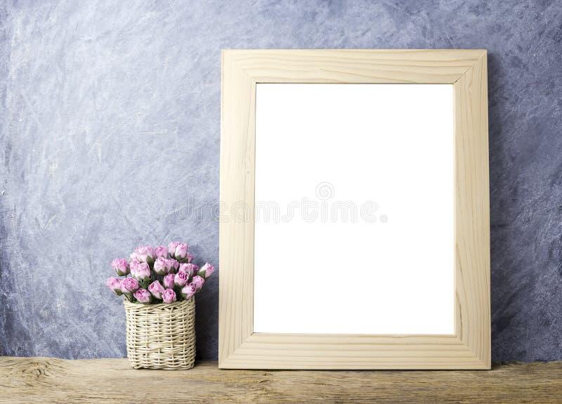 Flores cor-de-rosa do papel cor-de-rosa na cesta e na moldura para retrato vazia fotos de stock royalty free