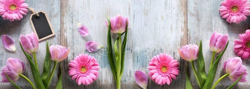 Flores cor-de-rosa em pranchas cinzentas do vintage fotografia de stock