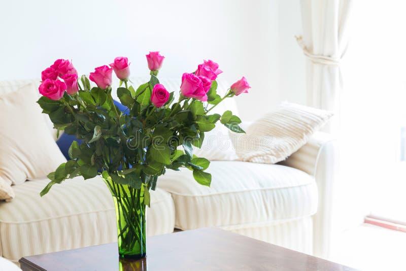Flores cor-de-rosa perfeitas em uma tabela na sala de visitas branca na frente de imagens de stock