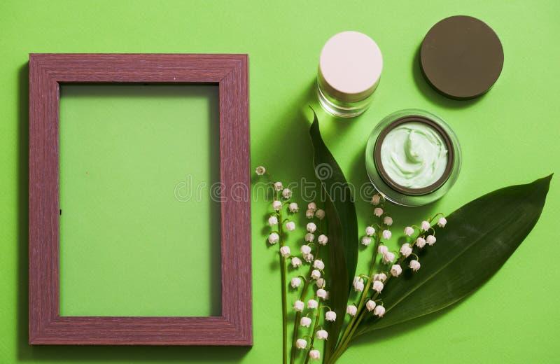 flores cosméticas de la crema y del lirio de los valles en un fondo verde fotos de archivo