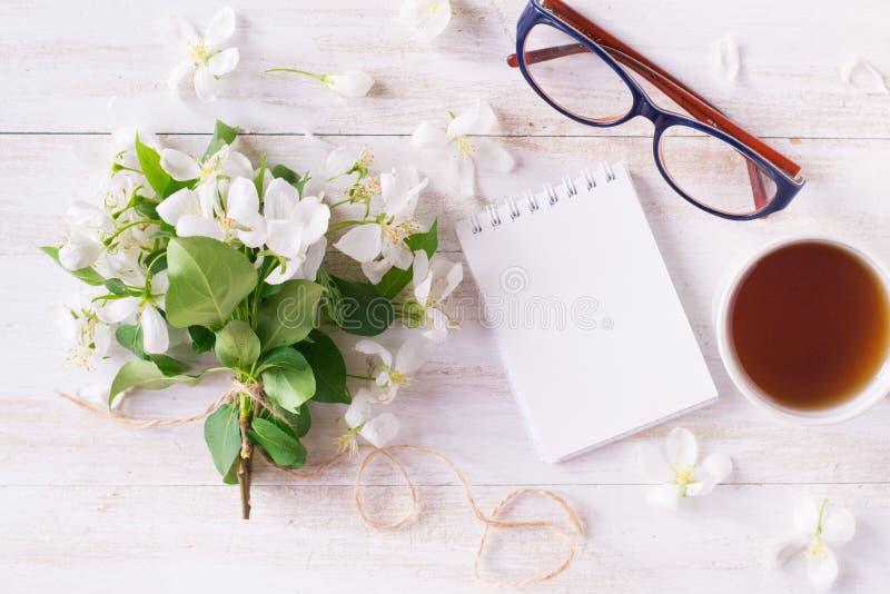 Flores da árvore de maçã, caderno, copo do anúncio dos vidros do chá fotos de stock royalty free