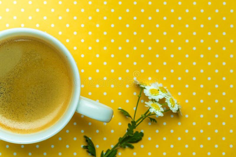 Flores da camomila e uma xícara de café em um fundo amarelo do às bolinhas imagens de stock