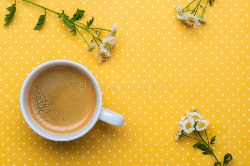 Flores da camomila e uma xícara de café em um fundo amarelo do às bolinhas foto de stock