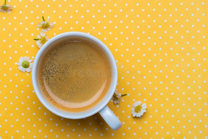 Flores da camomila e uma xícara de café em um fundo amarelo do às bolinhas fotos de stock royalty free