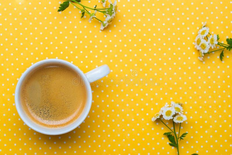 Flores da camomila e uma xícara de café em um fundo amarelo do às bolinhas foto de stock royalty free