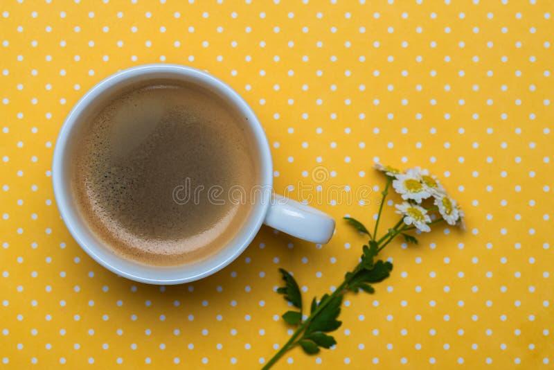Flores da camomila e uma xícara de café em um fundo amarelo do às bolinhas fotografia de stock