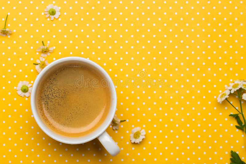 Flores da camomila e uma xícara de café em um fundo amarelo do às bolinhas imagem de stock