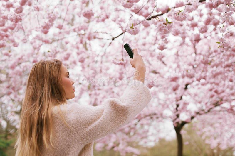 Flores da flor do tiro da jovem mulher com seu telefone celular foto de stock