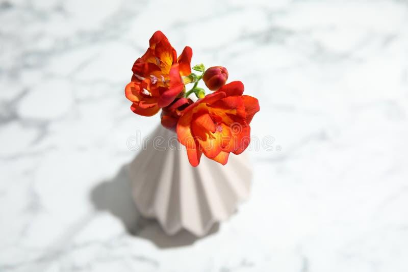 Flores da frésia da mola no vaso no fundo de mármore fotografia de stock