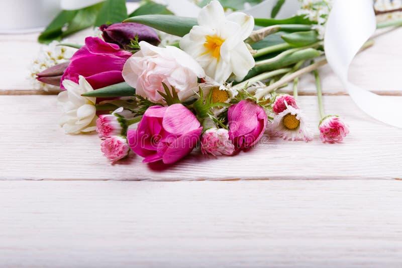 Flores da mola do ramalhete primeiras, rosa, tulipas roxas, narcisos amarelos e margaridas no fundo de madeira branco fotos de stock