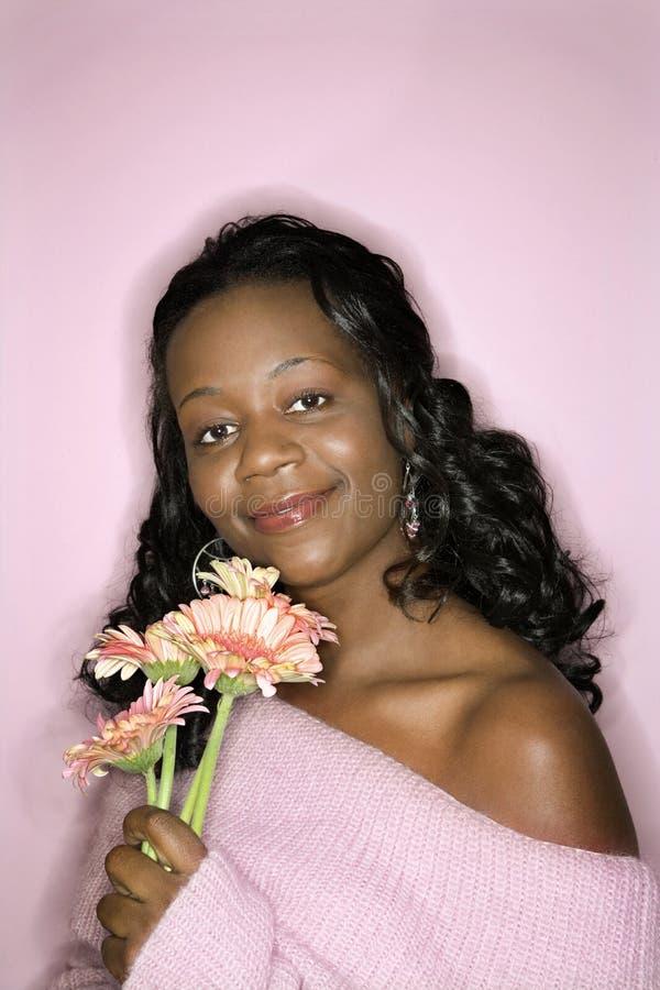 Flores da terra arrendada da mulher do African-American. imagem de stock