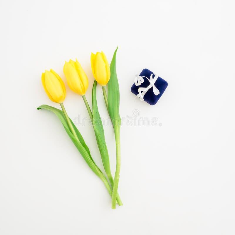 Flores da tulipa e caixa amarelas do anel no fundo branco Configuração lisa, vista superior imagens de stock