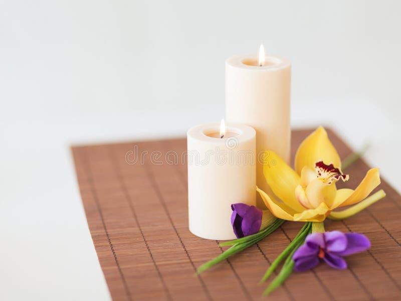 Flores das velas, da orquídea e da íris na esteira de bambu fotografia de stock