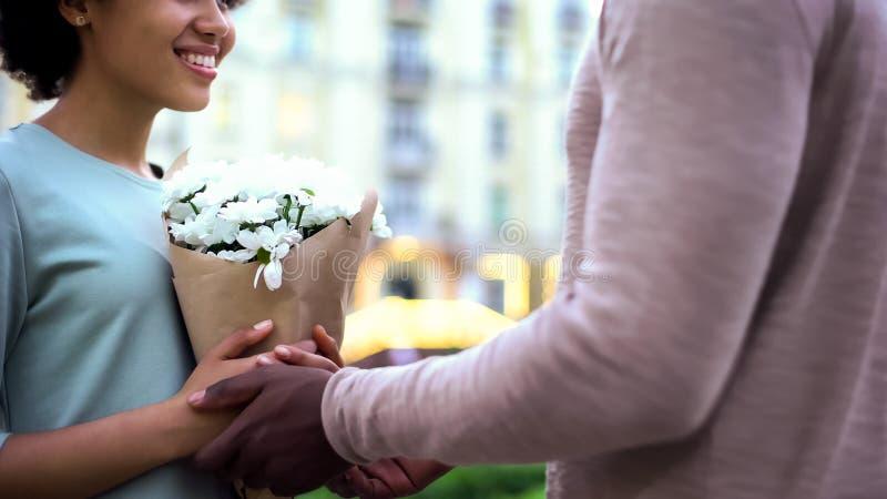 Flores de apresentação masculinas à amiga bonita, abraçando na data do verão, surpresa fotografia de stock