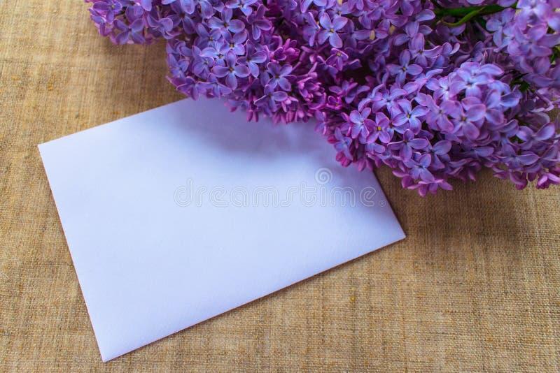 Flores de la lila en un florero de la lila y un sobre con un lugar para una inscripción postal imagenes de archivo