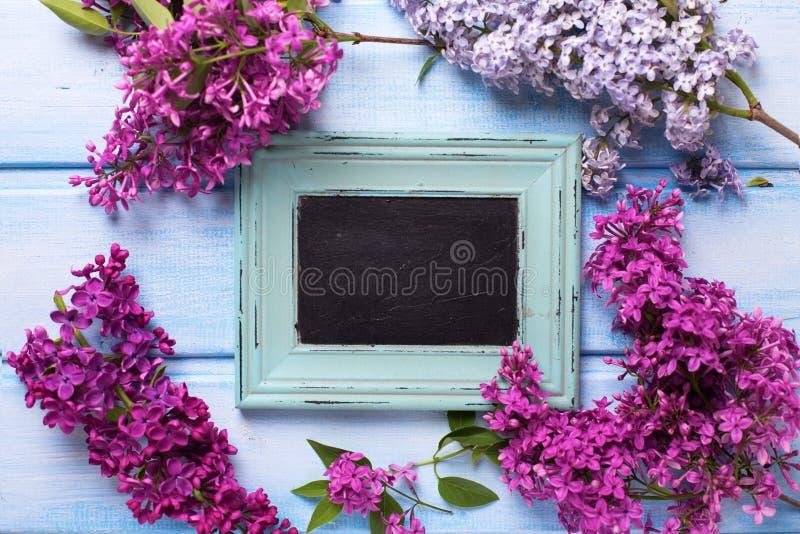 Flores de la lila y pizarra vacía en tablones de madera azules fotografía de archivo libre de regalías