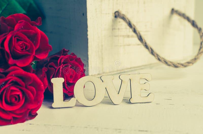 Flores de las rosas rojas con la palabra de madera AMOR foto de archivo libre de regalías