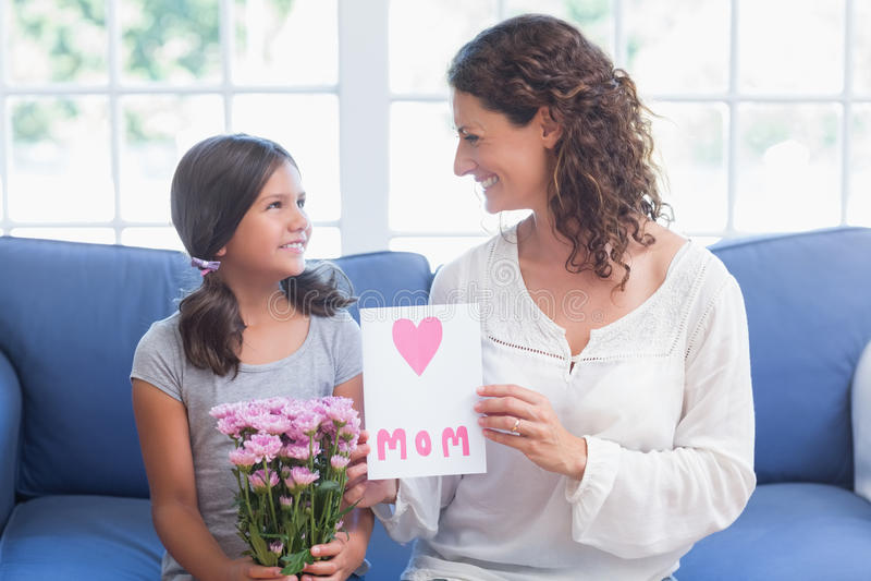 Flores de oferecimento e cartão da menina bonito a sua mãe foto de stock royalty free