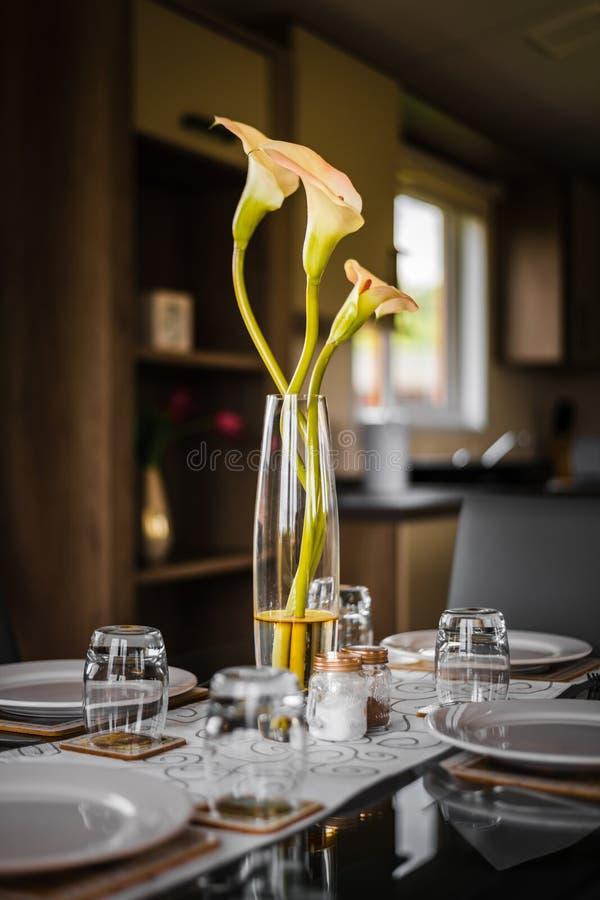 Flores de oro y blancas en un florero de los glasss sentarse como decoración en una tabla imagenes de archivo