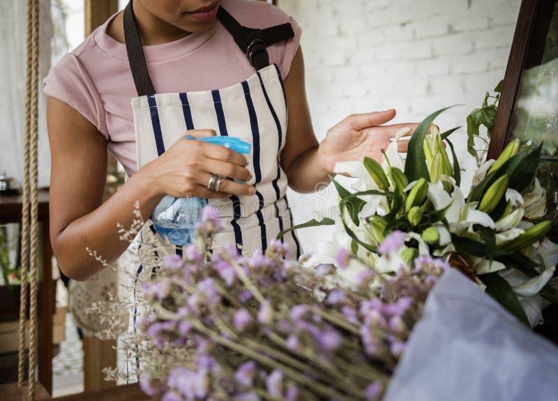 Flores de pulverização da mulher ao refrescamento em Flora Shop imagens de stock