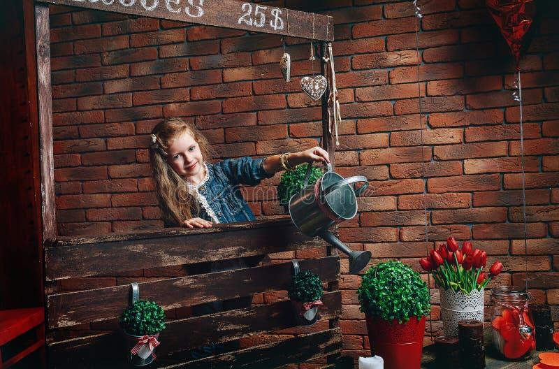 Flores de riego de la niña linda en casa foto de archivo libre de regalías
