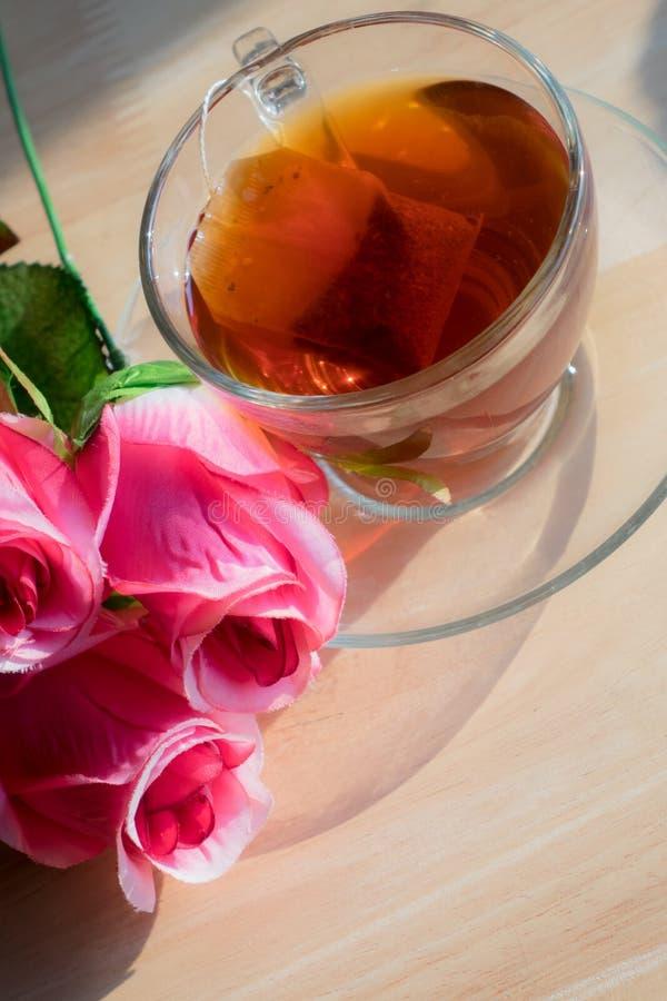 Flores de Rose con té caliente en la tabla imagen de archivo libre de regalías