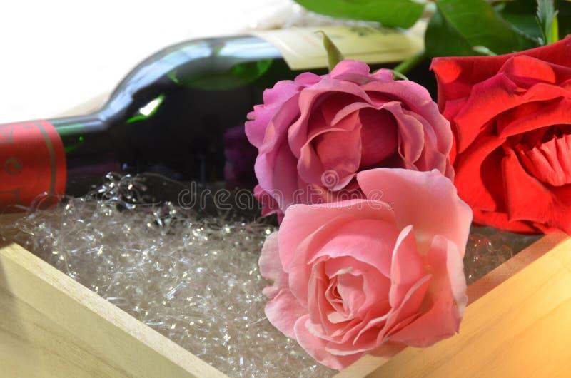 Flores de Rose y botella de vino fotografía de archivo libre de regalías