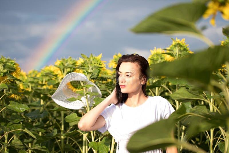 Flores del arco iris de la muchacha muchacha en el campo que sostiene un ramo de girasoles foto de archivo