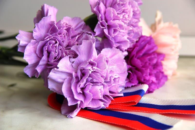 Flores del clavel ramo de flores, claveles violeta, lila y claveles rosados de las flores en el ramo cinta blanco-rojo-azul imágenes de archivo libres de regalías