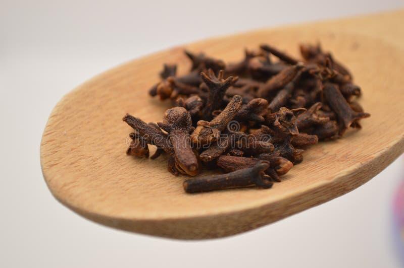 Flores del clavo en el ingrediente de madera de las especias de la cuchara para la nutrición de la cocina de la comida fotografía de archivo libre de regalías