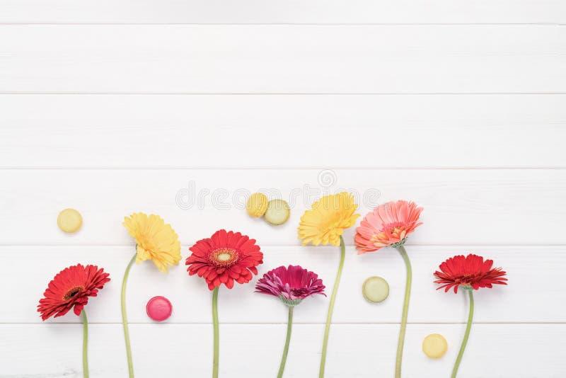 Flores del gerbera y macarrones rojos, amarillos en fondo de madera imágenes de archivo libres de regalías