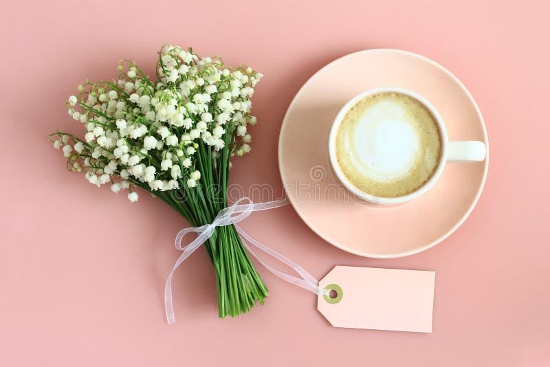 Flores del lirio de los valles y taza de café en fondo rosado en colores pastel foto de archivo